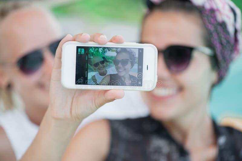 Duas amigas felizes nos óculos de sol que fazem o selfie foto de stock
