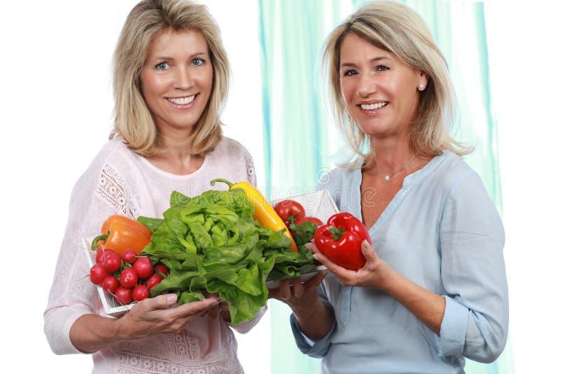 Duas amigas maduras com legumes frescos imagens de stock royalty free