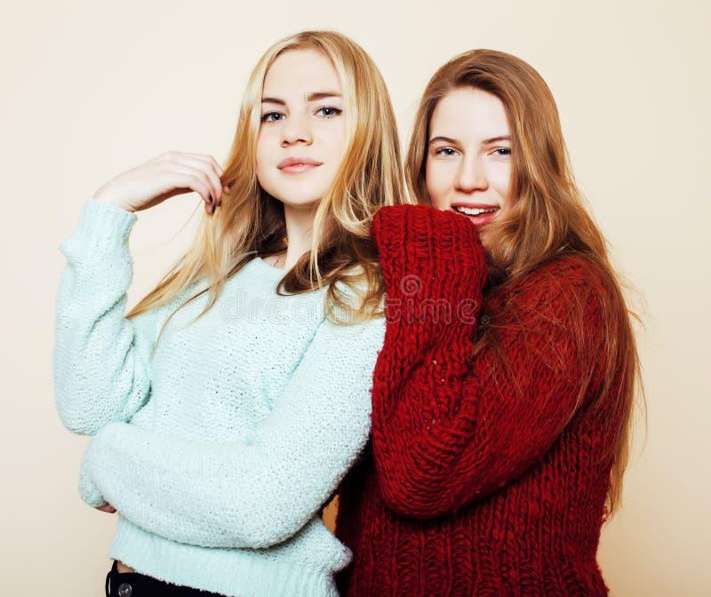 Duas amigas novas nas camisetas do inverno dentro que têm o divertimento Lif fotografia de stock