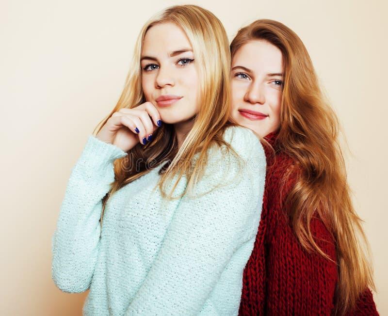 Duas amigas novas nas camisetas do inverno dentro que têm o divertimento Lif imagem de stock
