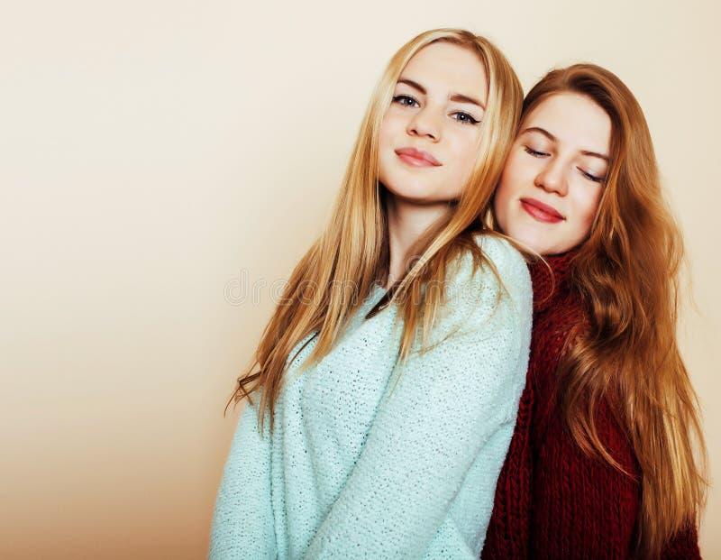 Duas amigas novas nas camisetas do inverno dentro que têm o divertimento Lif fotos de stock royalty free