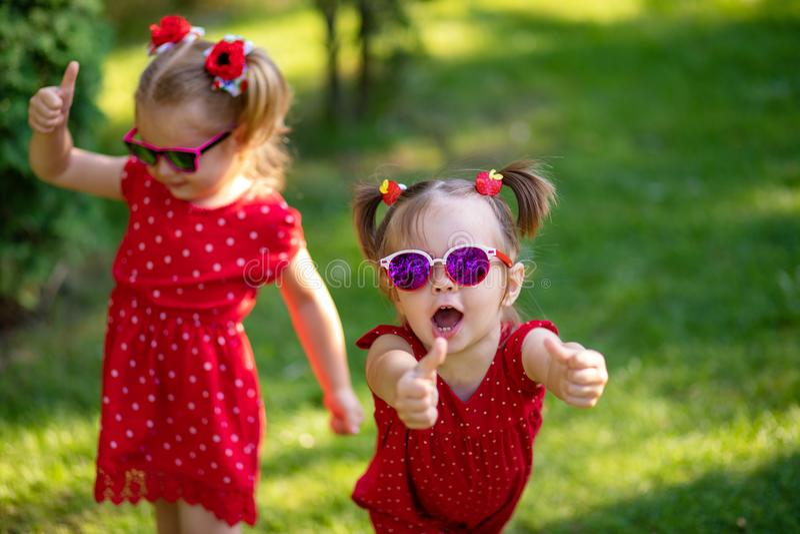 Duas amigas pequenas bonitos que têm o divertimento na jarda a vista da mostra da menina manuseia a sorte ascendente e boa vestid foto de stock