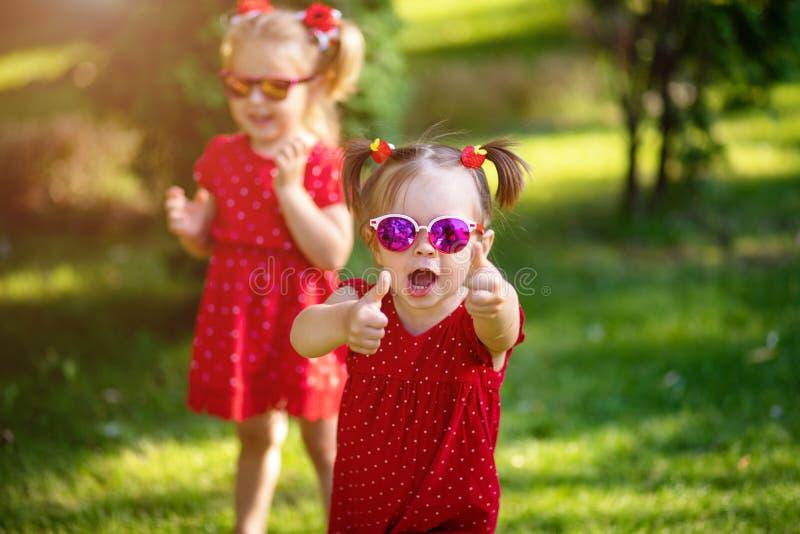 Duas amigas pequenas bonitos que têm o divertimento na jarda a vista da mostra da menina manuseia a sorte ascendente e boa vestid fotografia de stock