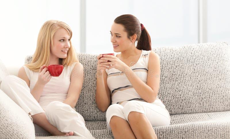 Duas amigas que conversam com os copos de café no sofá foto de stock