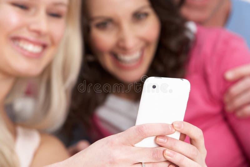 Duas amigas que olham retratos em Smartphone imagem de stock royalty free
