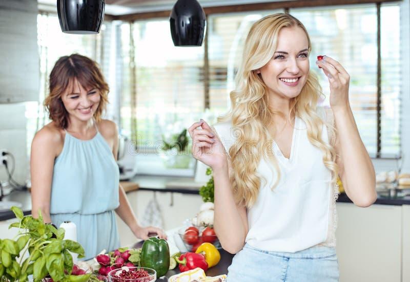 Duas amigas que relaxam na cozinha brilhante foto de stock royalty free