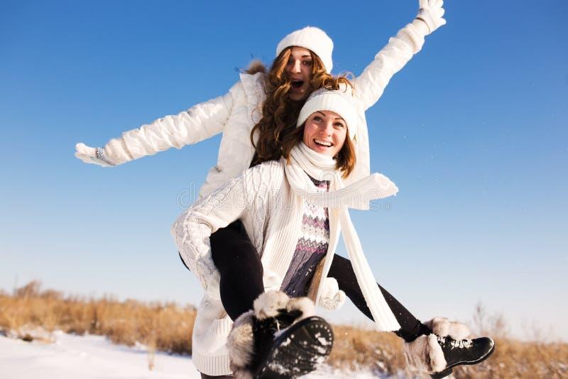 Duas amigas têm o divertimento e apreciam a neve fresca fotos de stock royalty free