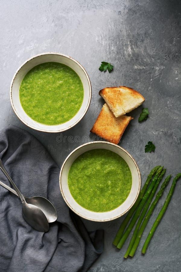Duas bacias de sopa de creme verde do aspargo com brindes friáveis em um fundo cinzento Vista a?rea, espa?o da c?pia fotografia de stock royalty free