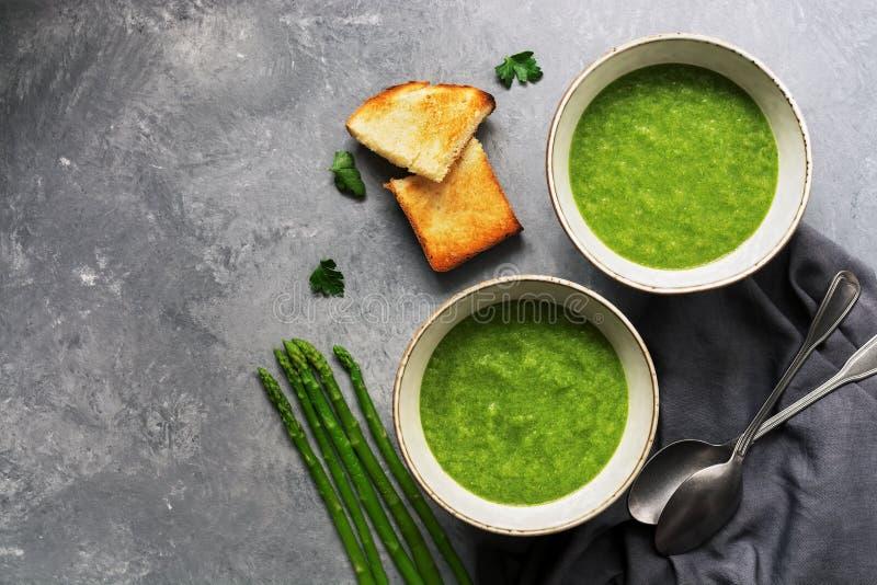 Duas bacias de sopa de creme verde do aspargo com brindes fri?veis em um fundo cinzento Vista a?rea, espa?o da c?pia imagem de stock royalty free