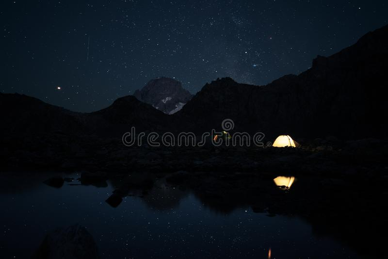 Duas barracas de incandescência nas montanhas altas na noite sob o céu estrelado imagens de stock royalty free