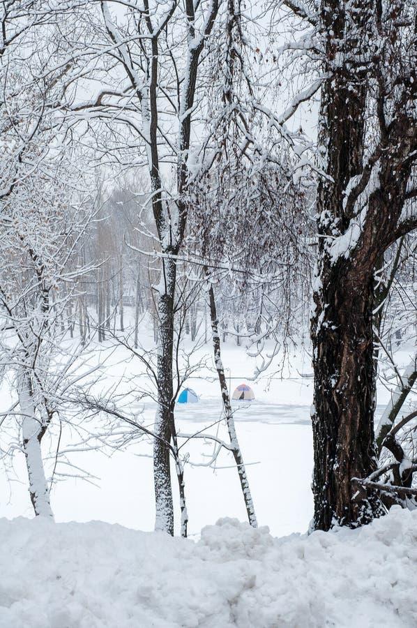 Duas barracas de pesca na distância no inverno no gelo de uma lagoa fotos de stock royalty free