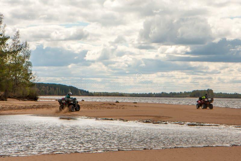 Duas bicicletas do quadrilátero com cavaleiros montam ao longo da costa com uma vista bonita imagens de stock