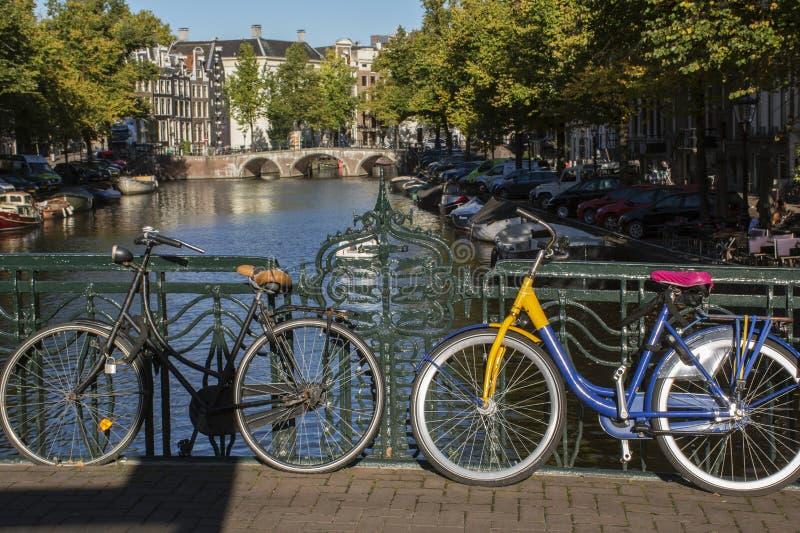 Duas bicicletas no dia do outono em Amsterdão com construções e ponte foto de stock royalty free