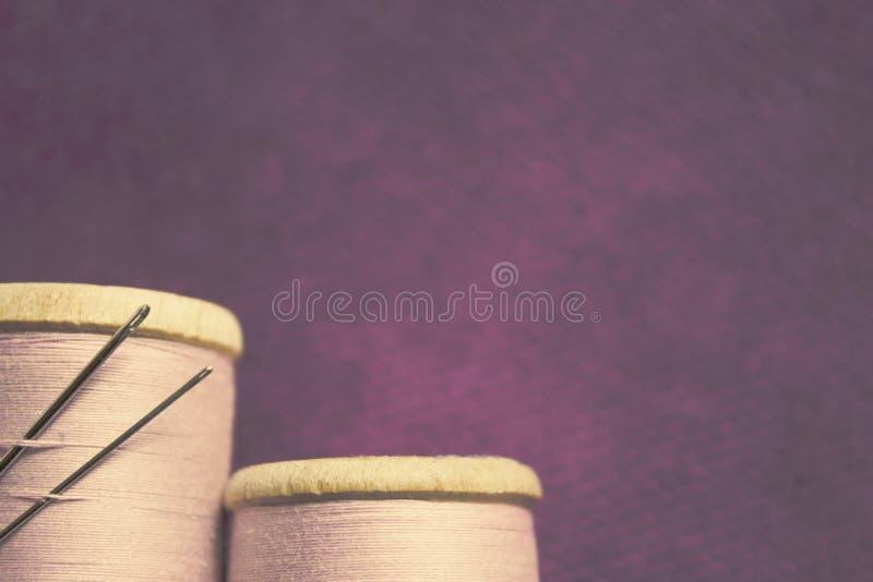 Duas bobinas com as linhas de alturas diferentes e com as duas agulhas coladas na bobina no fundo da imagens de stock royalty free