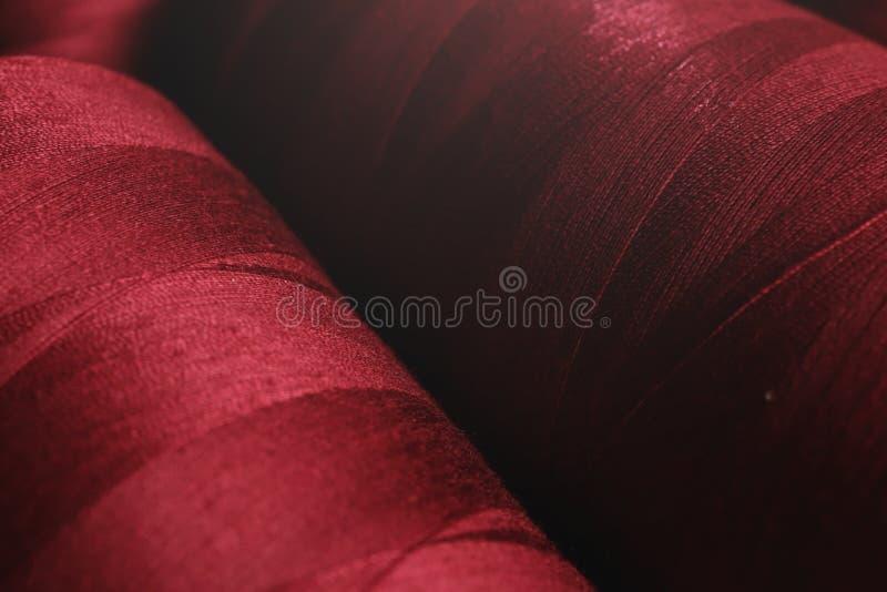 duas bobinas com a ferida pura profunda - linha vermelha na luz brilhante fotografia de stock