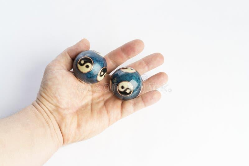 Duas bolas chinesas azuis de yang do yin à disposição no fundo branco imagem de stock royalty free