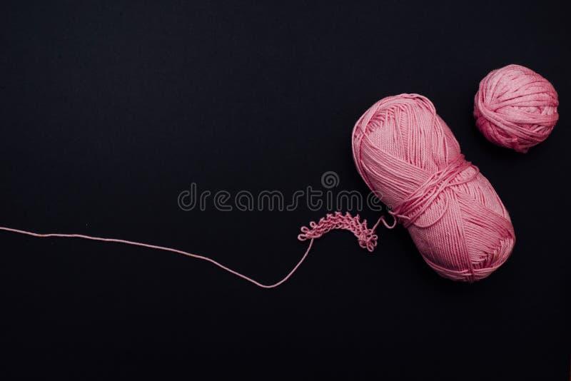 Duas bolas de algodão cor-de-rosa e algum teste padrão feito malha no lado direito de um fundo preto imagens de stock royalty free