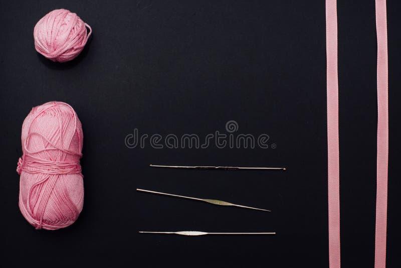 Duas bolas de algodão cor-de-rosa, duas fitas cor-de-rosa, três ganchos de confecção de malhas em um fundo preto imagem de stock