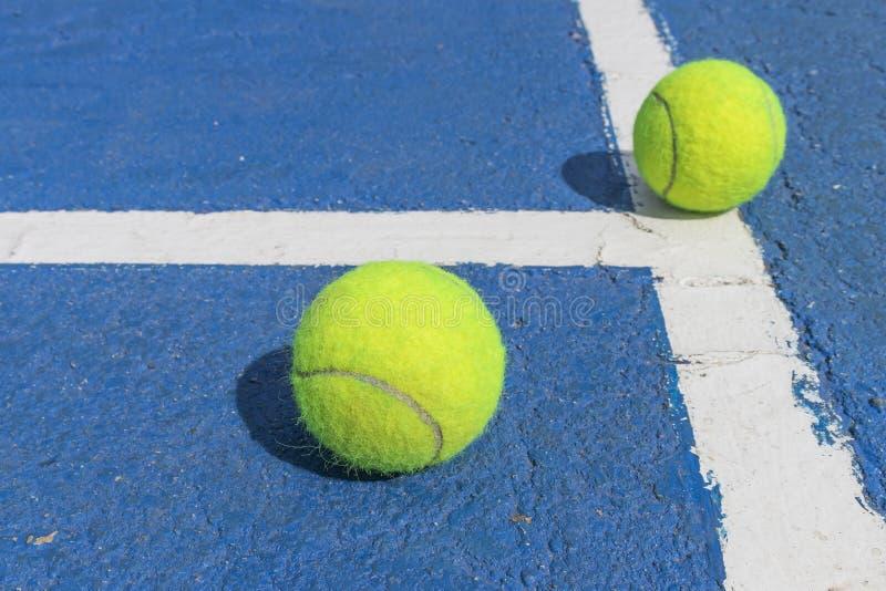 Duas bolas de tênis em um campo de tênis azul com linhas de marcação brancas imagem de stock