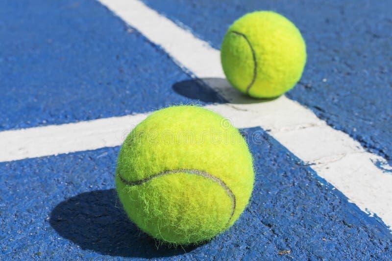 Duas bolas de tênis em um campo de tênis azul com linhas de marcação brancas fotografia de stock royalty free