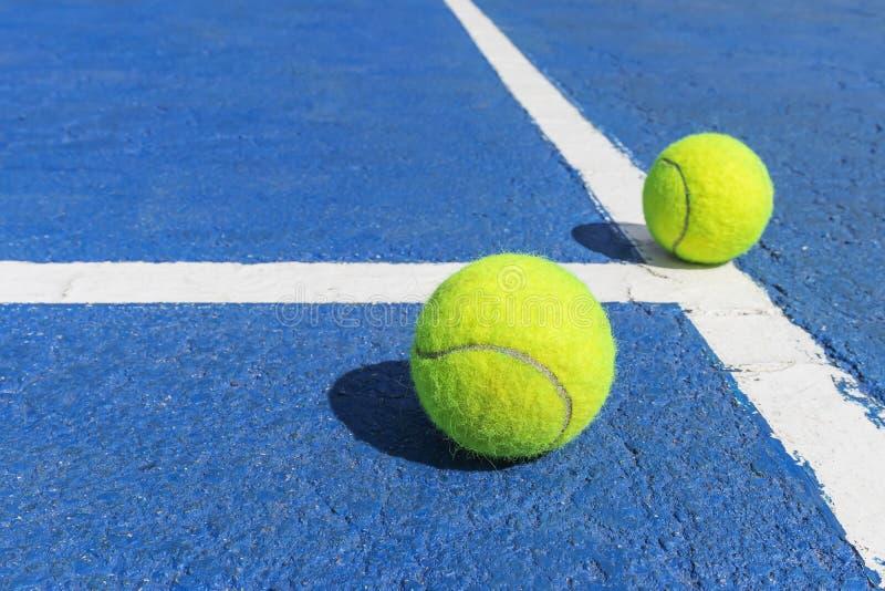 Duas bolas de tênis em um campo de tênis azul com linhas de marcação brancas foto de stock royalty free
