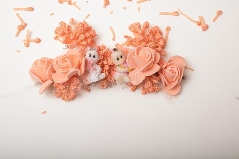Duas bonecas bonitos que sentam-se na frente do garla das flores artificiais imagens de stock