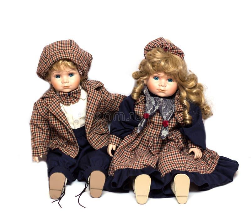 Duas bonecas cerâmicas dos jardineiro que sentam-se no fundo branco imagens de stock royalty free