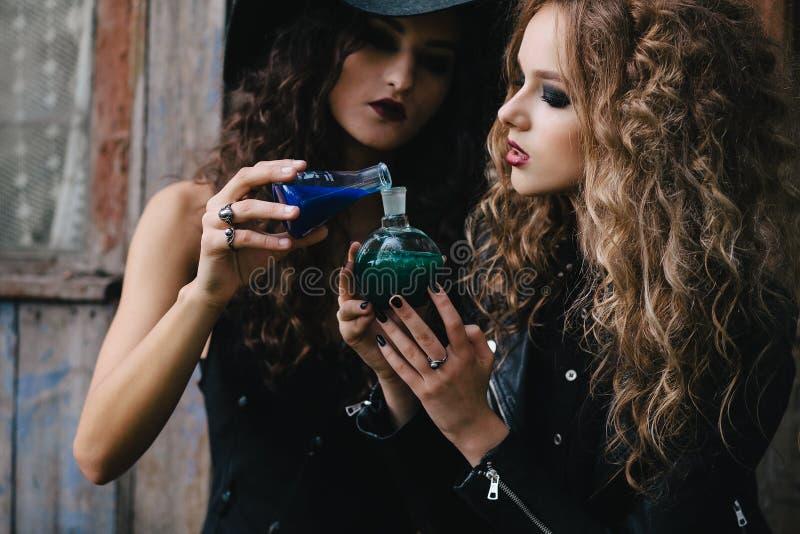 Duas bruxas do vintage executam o ritual mágico fotografia de stock