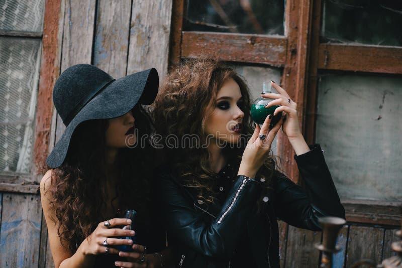 Duas bruxas do vintage executam o ritual mágico imagens de stock
