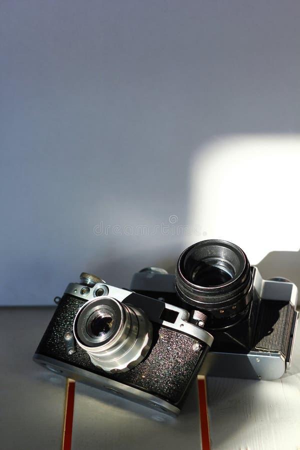Duas câmeras pretas da foto do vintage da velha escola nas pranchas de madeira brancas, interior ensolarado fotografia de stock