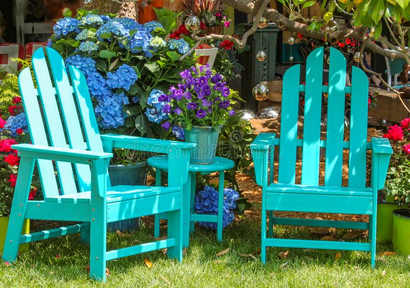 Duas cadeiras de Adirondack de turquesa e uma tabela de harmonização cercada por flores bonitas e pelas bolas do espelho das árvo fotografia de stock