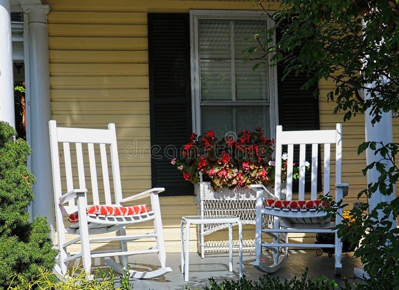 Duas cadeiras de balanço brancas estão no pátio de entrada coberto de uma casa amarela imagem de stock royalty free