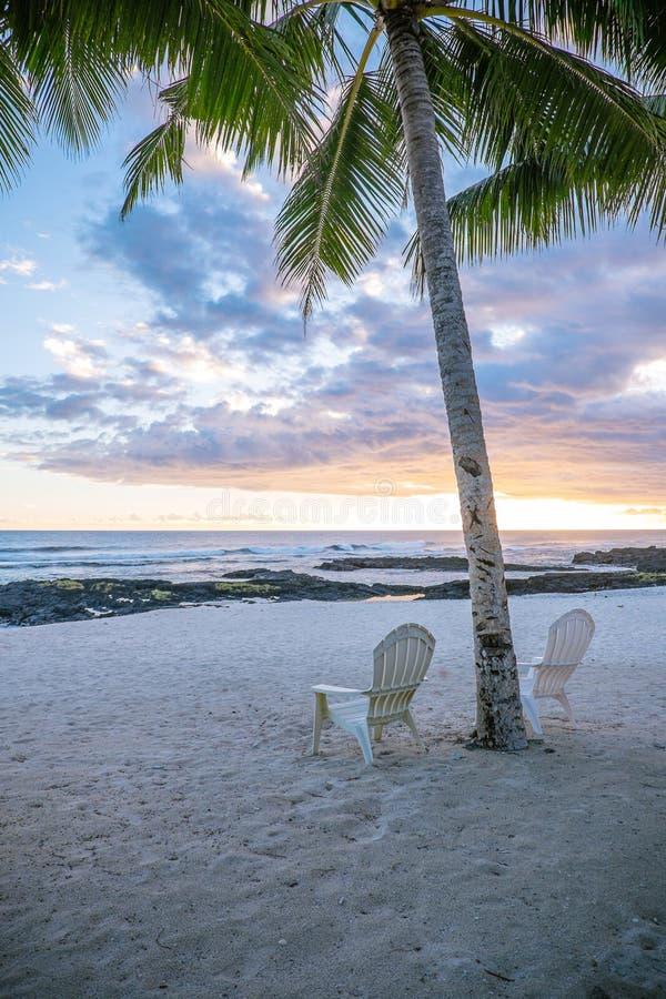 Duas cadeiras de plataforma sob a palmeira no por do sol em uma praia vazia em L imagens de stock royalty free