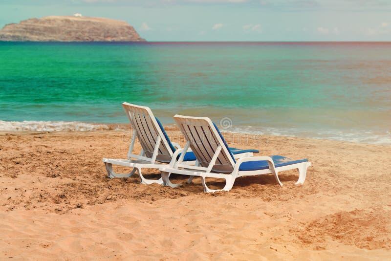 Duas cadeiras de plataforma vazias em um Sandy Beach abandonado no oceano fotografia de stock royalty free
