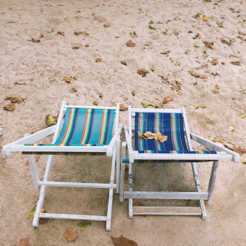 Duas cadeiras de plataforma vazias na praia, conceito das férias de verão foto de stock