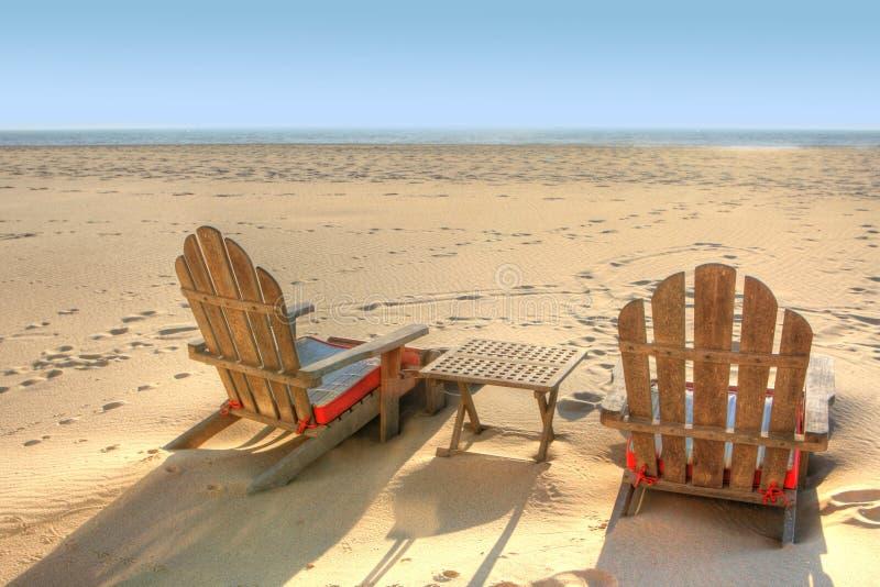 Duas cadeiras de praia que sentam-se na areia fotografia de stock royalty free