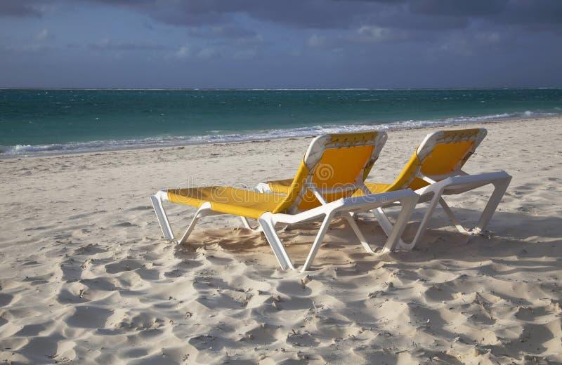 Duas cadeiras de sala de estar amarelas vazias na praia imagem de stock