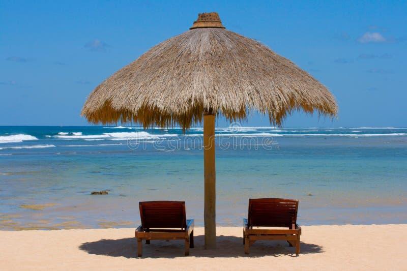 Duas cadeiras de sala de estar sob a barraca na praia imagens de stock