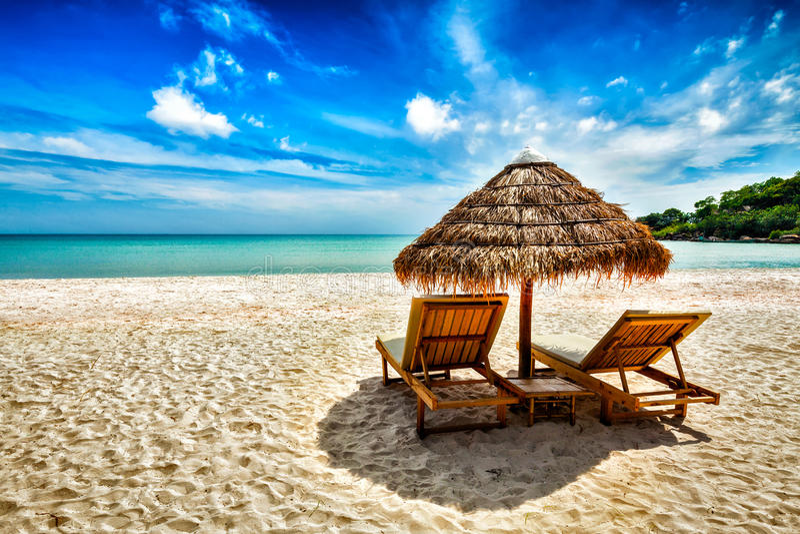 Duas cadeiras de sala de estar sob a barraca na praia imagem de stock royalty free