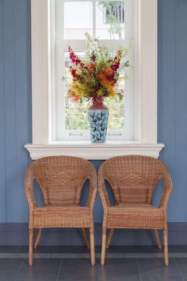 Duas cadeiras do rattan com vaso e janela foto de stock