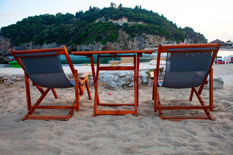 Duas cadeiras e a tabela no Sandy Beach Conceito do feriado com relaxamento na praia imagem de stock royalty free