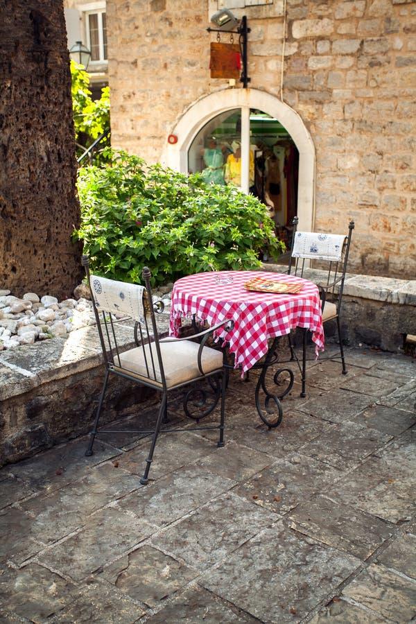Duas cadeiras e tabelas no terraço do verão do restaurante velho imagens de stock