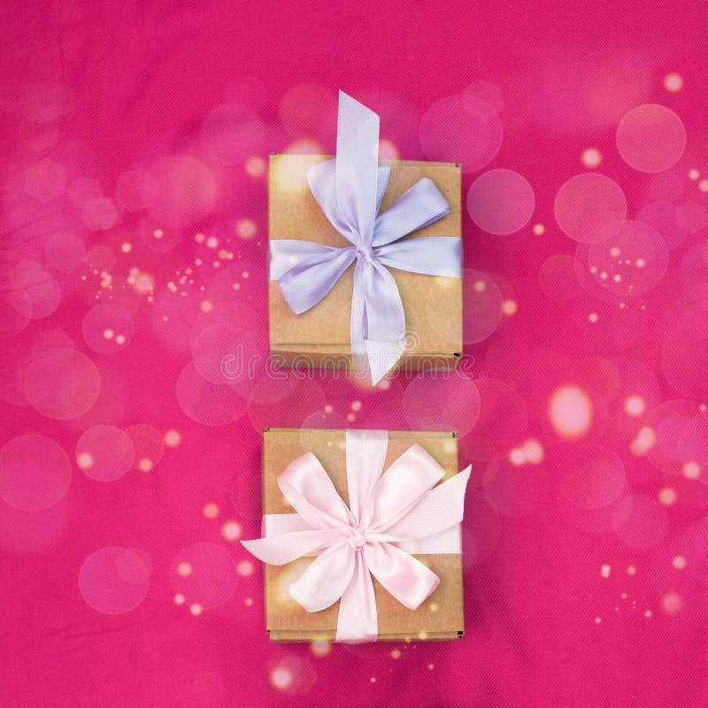 Duas caixas de presente amarradas com cetim coloriram a fita em um fundo cor-de-rosa um coração vermelho imagem de stock