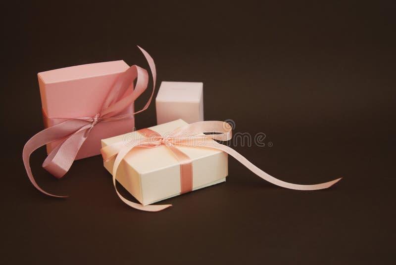 Duas caixas de presente com uma curva cor-de-rosa isolada no fundo marrom Presente, aniversário Conceito da venda - mão com lupa  foto de stock