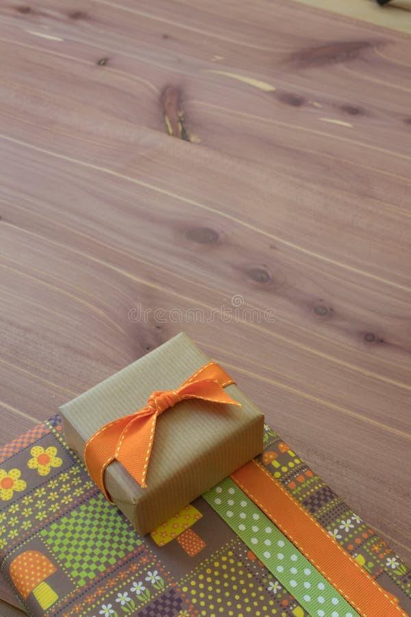 Duas caixas de presente empilhadas, papel de envolvimento retro com flores e cogumelos, laranja e marrom foto de stock royalty free