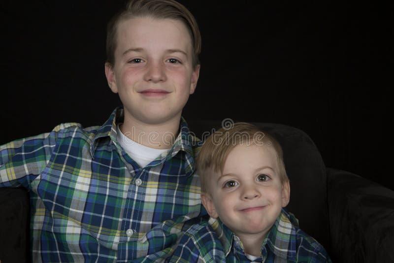 Duas camisas de harmonização vestindo do retrato bonito dos irmãos que sorriem no Ca imagem de stock