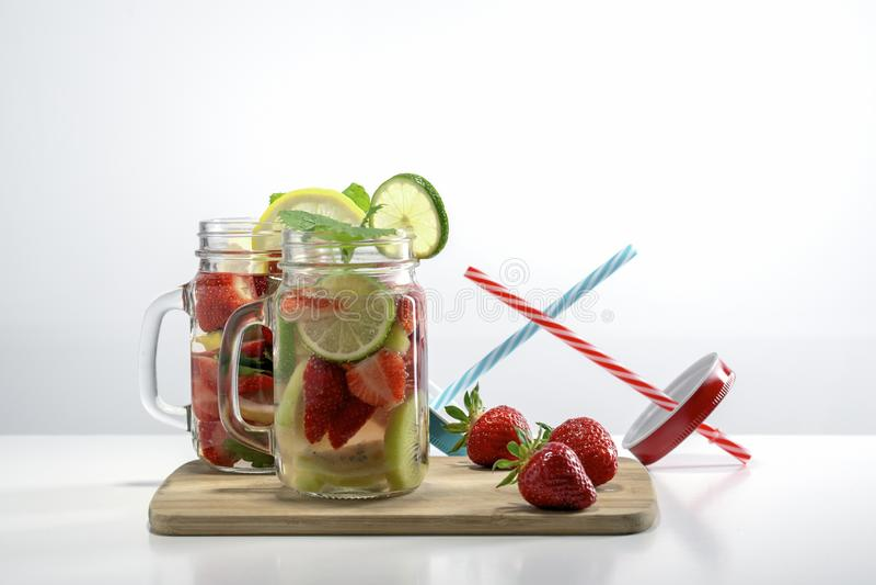 Duas canecas de água do fruto com morangos hortelã e de suporte do limão em um suporte de madeira ao lado das morangos e das cane imagem de stock