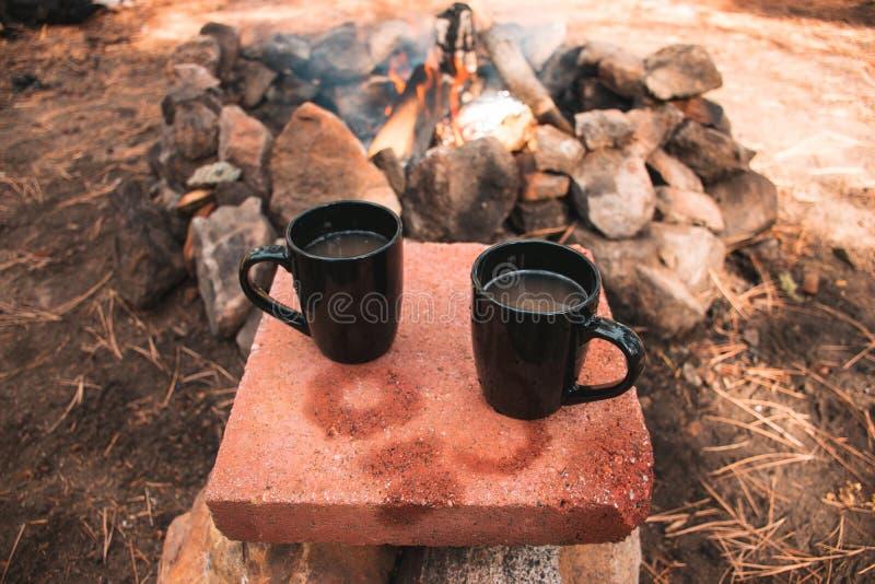 Duas canecas de café descansam no fazem o deslocamento apresentar ao acampar fotos de stock royalty free