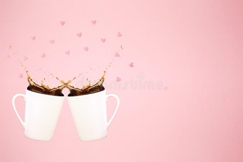 Duas canecas de café levitando com espirram e o confete do coração Conceito do café Tendência mínima da arte Fundo cor-de-rosa co imagem de stock