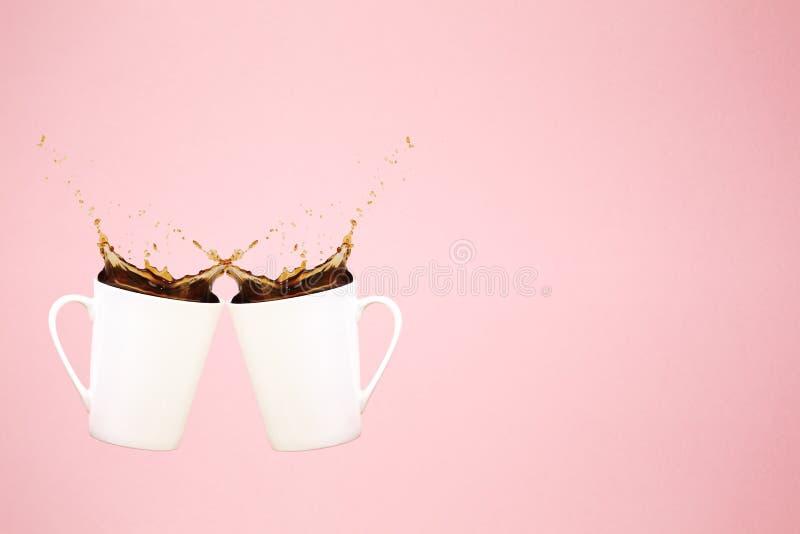Duas canecas de café levitando com espirram e o confete do coração Conceito do café Tendência mínima da arte Fundo cor-de-rosa co foto de stock